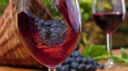 grape basket : Red wine is poured into a glass on a background full glass and of a basket of ripe grapes Stock Footage