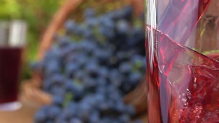 grape basket : Grape juice is pouring into a glass on a background of a basket of ripe grapes Stock Footage