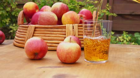 cidra : Apple juice and a basket of ripe apples on a wooden table. Slow motion. Vídeos