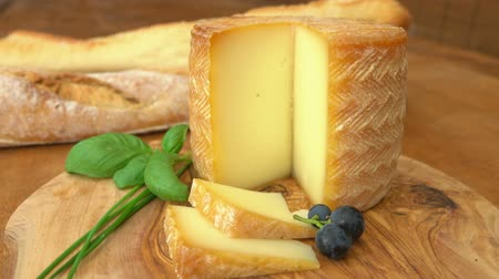 cheese types : pasteurised sheeps milk cheese made in French Basque region with a piece cut out on a wooden table