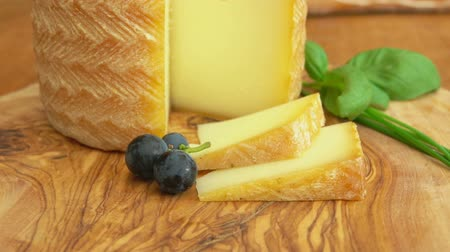 cheese types : Cheese head Etorki with a piece cut out on a wooden table