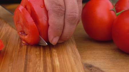 cebolas : Slicing tomatoes with knife on the wooden board