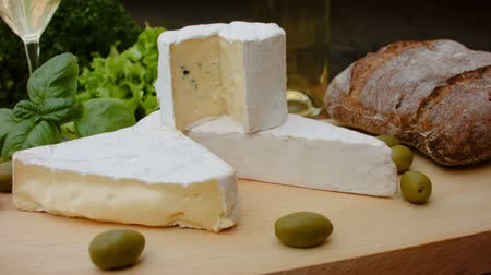 cheese types : Movement of the camera around of French brie cheese with bread, olives, basil and parsley