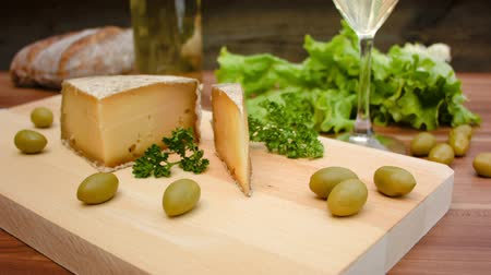 cheese types : Unpasteurised, semi-hard cheese made from sheeps milk with natural, crusty, brownish rind on a wooden board with herbs on background Stock Footage