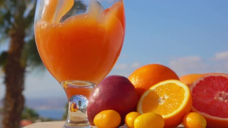 grejpfrut : Multifruit juice is poured into a wine-glass against the background of the sunny sea landscape, close-up camera motion Wideo