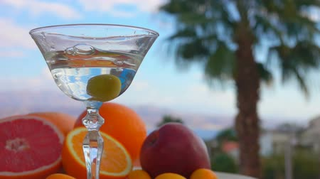 vermouth : Olive falls into a glass with martini on a background of citrus fruits and palm trees Stock Footage