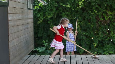 щетка для волос : Girls sweep the wooden floor on the open veranda