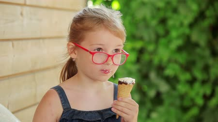 słodycze : Beautiful girl in glasses is eating ice cream