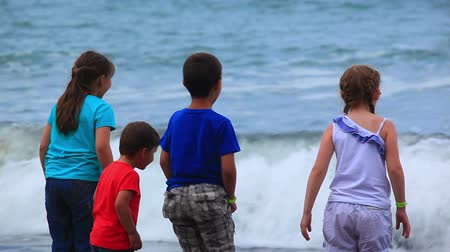 brothers : Girls and boys run away from the waves