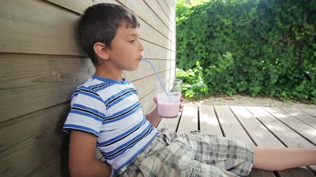 turmix : Boy drinks strawberry milk shake with a straw Stock mozgókép