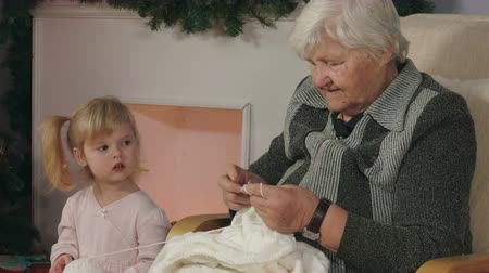 změť : Grandmother teaches to knit her granddaughter, sitting in a chair next to the fireplace. Christmas Eve, elegant Christmas tree