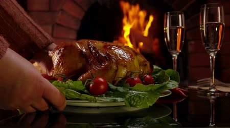 garnished : Celebratory dinner by the fireplace. Hands put a dish with chicken on a table with glasses of champagne.