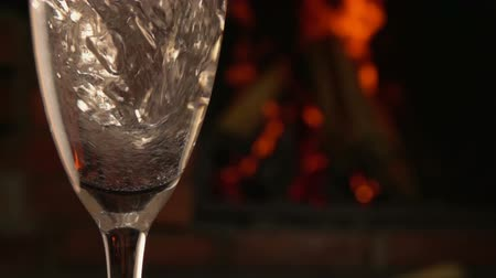 fuvolák : Champagne is poured into a glass on a background of fireplace