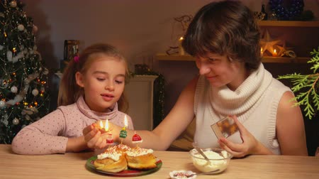 muffin : Mother and daughter light Christmas candles on cinnamon rolls
