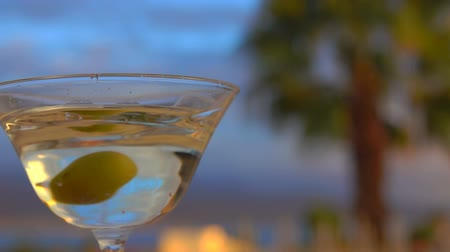 vermouth : Olive falls into a glass with martini on a background of palm trees