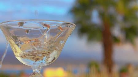 körítés : Vermouth martini is poured into a glass on a background of palm trees