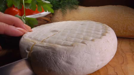 cheese types : Kitchen knife carves a sector of French round cheese Stock Footage