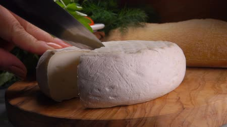 cheese types : Kitchen knife carves a sector of French round cheese. Pan movement of the camera
