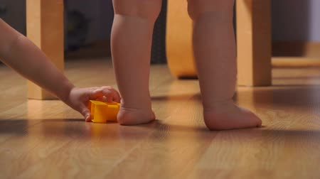 learning to walk : close-up of very small legs and arms near the chair on the floor