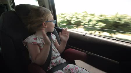 yönlendirmek : The little girl is riding in the car and clapping her hands