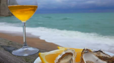 bivalve : Glass of white wine and a plate of oysters with lemon against the background of ocean waves on the quay Etretat, Normandy