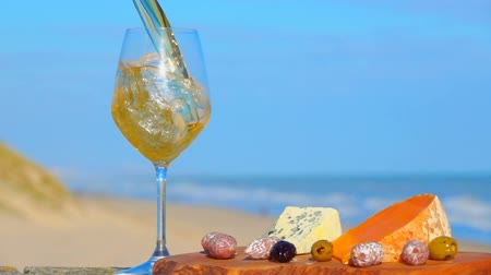 borgonha : Romantic picnic on the Atlantic coast with French cheeses and white wine. White wine is poured into a wine glass