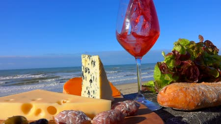 normandiya : Romantic picnic with Normandy cheese and snack on a wooden board in front of the Surf of the Atlantic Ocean. Red wine is poured into a wine glass