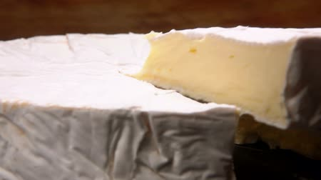 столовая гора : Knife lifts a sector of round brie cheese. Pan movement of the camera