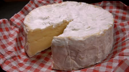 столовая гора : Knife lifts a sector of round Camembert cheese close up. Pan movement of the camera Стоковые видеозаписи