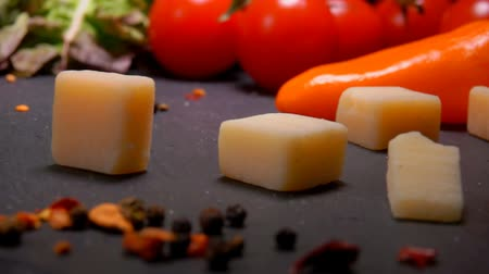 cheese types : Cubes of Parmesan cheese fall to the surface of the table on the background of greenery and vegetables