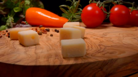 wooden type : Cubes of Parmesan cheese fall to the wooden board on the background of greenery and vegetables Stock Footage