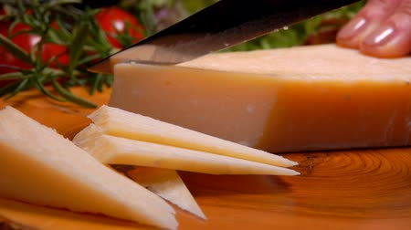 wooden type : Piece of hard Parmesan cheese cutting by knife into slices on a wooden board Stock Footage