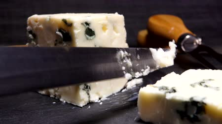 moldy : Knife cuts off a piece of Roquefort cheese on a black stone board close-up Stock Footage