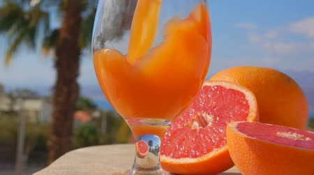 citron : Grapefruit juice is poured into a wine-glass against the background of the sunny sea landscape, close-up camera motion Stock Footage