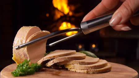 pasztet : Special knife cuts a piece of foie gras on a wooden board against the background of a burning fireplace
