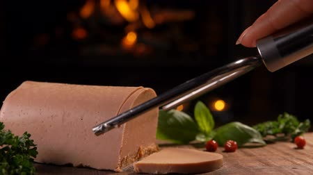 pasztet : Special knife cuts a slice of foie gras in the background of a burning fireplace