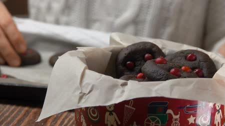 assar : Hand takes chocolate cookies with cranberries from a pan and puts them in a Christmas box