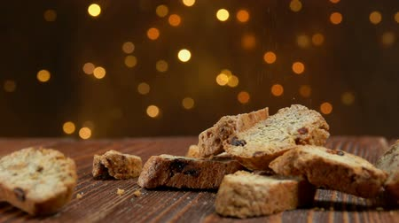 betűrendes : italian cantucci with almond and cranberries falls on a wooden surface against the background of Christmas light strings Stock mozgókép