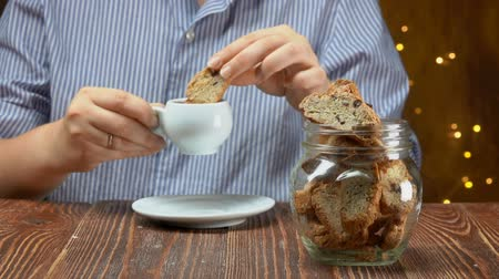 assar : Hand takes italian cantucci cookies with almond and cranberries from a glass jar and dunks it into an espresso cup