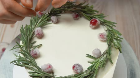 elegant dessert : Hand of confectioner decorates the cake with sugar cranberries and rosemary Stock Footage