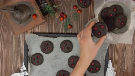assar : Top view on hand takes chocolate cookies with cranberries from a pan and puts them in a Christmas box