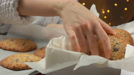 aveia : Hand takes oatmeal coockies from a pan and puts them in a Christmas box