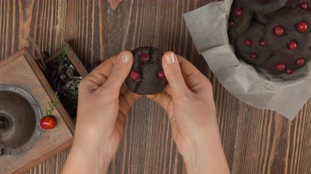 assar : Close-up on hands breaking chocolate cookies with cranberries top view
