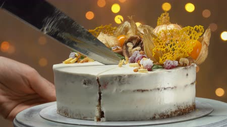 elegant dessert : Close-up of a hand with a knife cuts off a slice of carrot cake with salted caramel