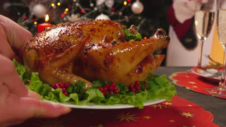 garnished : Close-up of hands to put on a festive table a dish with cooked chicken on the background of the Christmas tree. Stock Footage