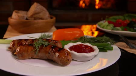 baharatlı alman sosisi : Hands put on the table a plate of dinner with grilled sausage on a background of a burning fireplace
