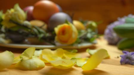 jacinto : Petals of a yellow rose fall on a table against a background of colored Easter eggs