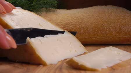 moldy : Knife cuts off a piece of soft sheeps cheese from whole milk