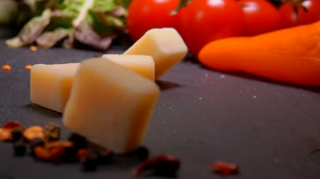 bagietka : Cubes of Parmesan cheese fall to the black surface of the table on the background of greenery and vegetables