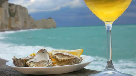 shellfish dishes : Glass of white wine and a plate of oysters with lemon on the Atlantic coast Stock Footage